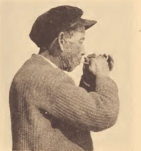 Pamunkey hunter demonstrating method of calling wild turkey with a wing-bone call